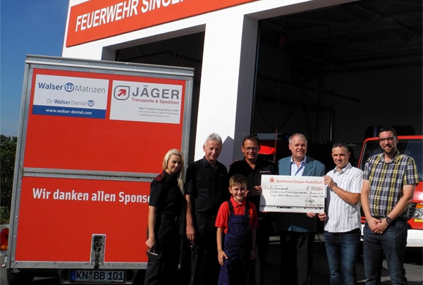 Beside the trailer f.l.t.r. Christina Salewski, youth group leader; Hubert Roth, deputy division commander; Linus Auer, member of the youth fire brigade; Stephan Einsiedler, division commander and 1st chairman; Senator h.c. Gerhard R. Daiger, Managing Director of Dr. Walser Dental; Mike Belcke, 2nd chairman; Christian Auer, Managing Director of Jäger Transporte & Spedition